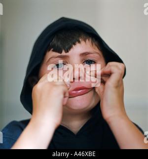 Boy making faces - Stock Photo