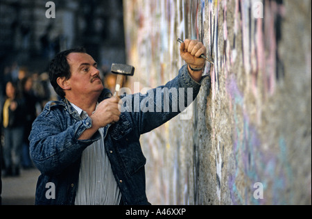 Fall of the Berlin Wall: man chiselling pieces off the Wall (Mauerspecht), Berlin, Germany - Stock Photo