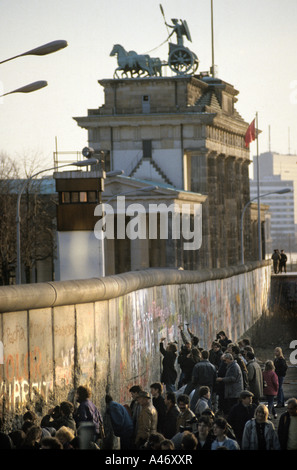 Fall of the Berlin Wall: people chiselling pieces off the Wall at the Brandenburg Gate (Mauerspecht), Berlin, Germany - Stock Photo