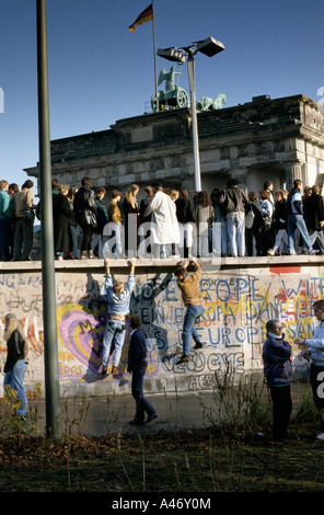 Fall of the Berlin Wall: people from East and West Berlin climbing on the Wall at the Brandenburg Gate, Berlin, - Stock Photo