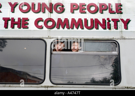 Two cheeky smiling girls look out of the window of a community bus - Stock Photo