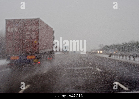 Bad driving conditions in snow and  wet weather seen through car windscreen on British motorway, England, UK - Stock Photo