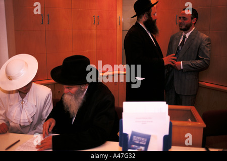 An orthodox Jewish couple couple sign legal marriage documents with a rabbi in Jerusalem Israel - Stock Photo