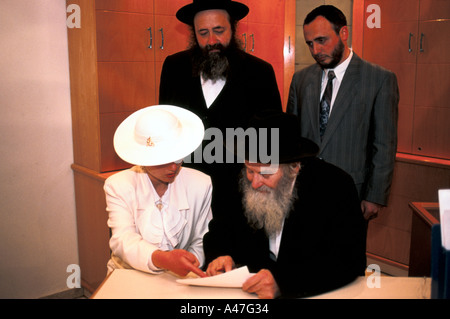 A Jewish couple sign legal marriage documents before a Rabbi at their wedding in a synagogue in Jerusalem, Israel - Stock Photo