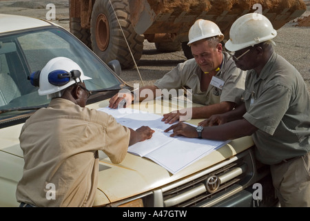 Mining engineers leaning over front of car in discussions about gold production on surface gold mine, Ghana, West - Stock Photo