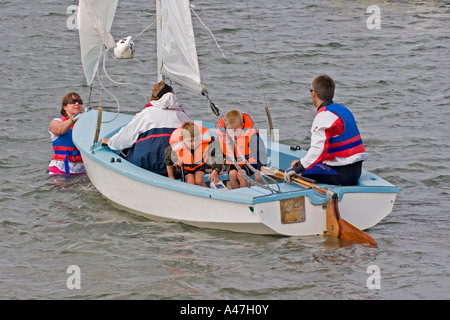 Family in boat preparing to set sail before sailing, Bosham, West Sussex, South of England, UK, - Stock Photo