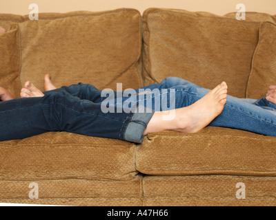 Couple reclining on sofa - Stock Photo