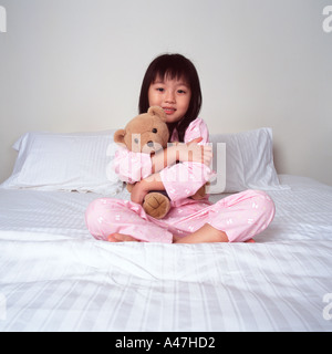 Young girl cuddling bear on bed - Stock Photo