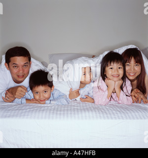 Happy young family in bed - Stock Photo
