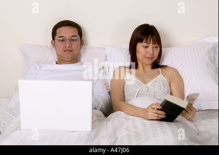 Couple in bed reading - Stock Photo