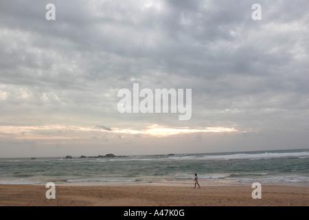 A tourist walks along the sea shore on the beach in Hikkaduwa in Sri Lanka - Stock Photo