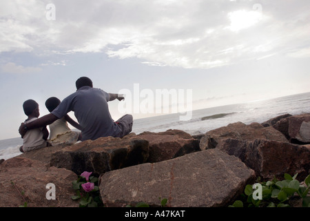 A father and his twin daughters visit the beach everyday to cherish the memory of their family members who died - Stock Photo