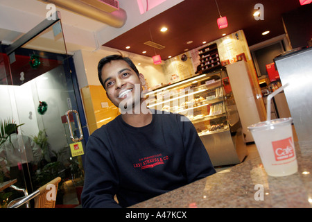 A young Indian man who works in the it industry sits in a modern cafe in Bangalore in India - Stock Photo