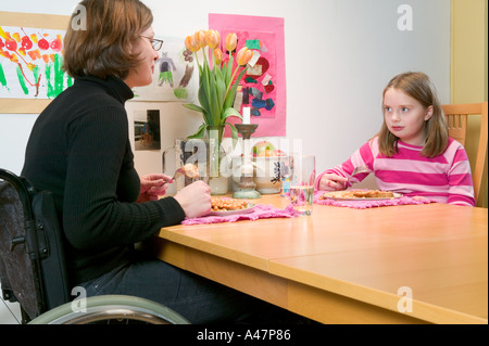 Mother and daughter eating beans on toast - Stock Photo