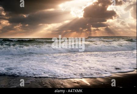 A stormy sunrise over a beach in Torquay in South Devon - Stock Photo