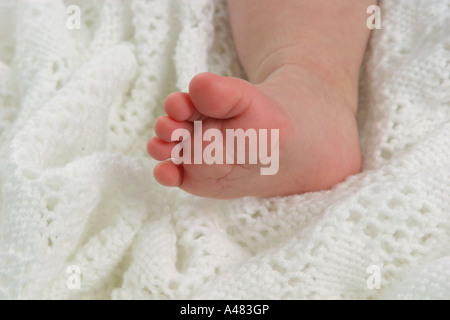 Baby's foot resting on a white shawl - Stock Photo