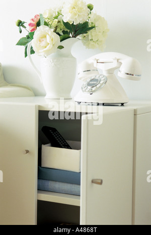 Close-up of a telephone with a flower vase on a cabinet - Stock Photo