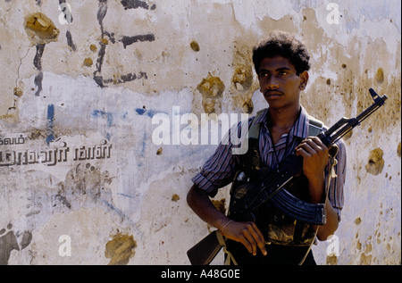 A Tamil tiger commando poses in front of a wall of political slogans Jaffna Peninsula Sri Lanka - Stock Photo