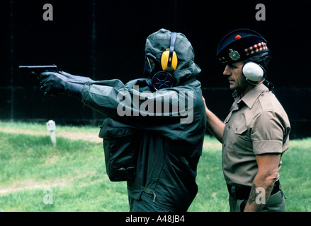 A soldier training for chemical warfare is instructed how to use small arms while wearing a nuclear and chemical - Stock Photo