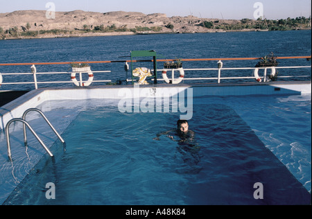 Passenger swimming in a pool on the top deck of the cruise ship Soleil as it travels between Luxor and Aswan Egypt - Stock Photo