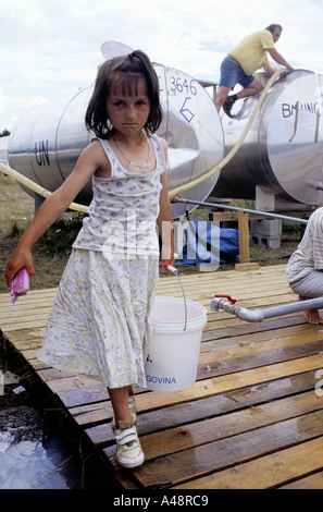 Refugee girl  from srebrenica collecting water  from a standpipe july 1995  .Tuzla aerodrome refugee camp - Stock Photo