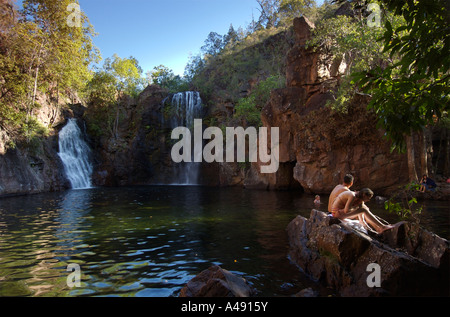 A couple sits on a rock beside a swimming hole in Australia's Northern Territory - Stock Photo