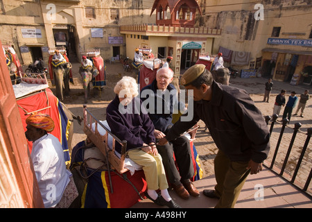 India Rajasthan Amber Fort old western couple boarding elephant for ride up steep fort road - Stock Photo