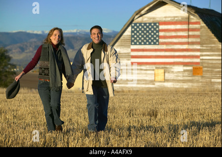 Man and woman smiling walking through cut grass fields in Fall with barn and american flag Colorado - Stock Photo
