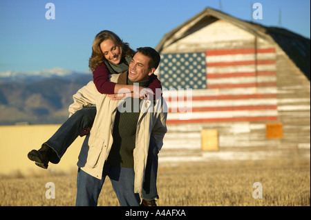Woman on mans back smiling in cut grass fields in Fall with barn and american flag Colorado - Stock Photo