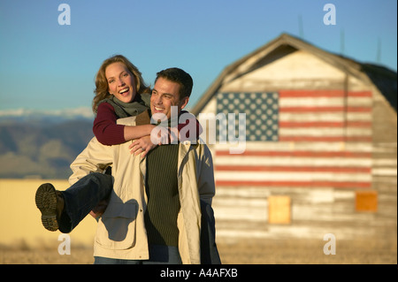 Woman on mans back laughing in cut grass fields in Fall with barn and american flag Colorado - Stock Photo