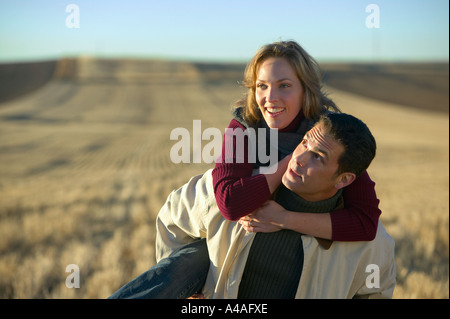 Woman laughing on mans back in cut grass fields in Fall Colorado - Stock Photo
