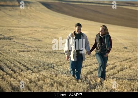 Couple smiling holding hands walking through fields of cut golden grass in Fall Colorado early morning - Stock Photo