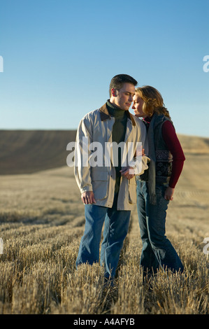 Woman leaning on man in fields of golden cut grass in Fall Colorado early morning Autumn - Stock Photo