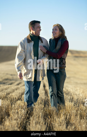 Couple laughing and walking through fields of cut grass in Fall Colorado early morning - Stock Photo