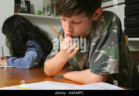 An eight year old boy doing his maths homework at home with his sister in the background doing her own homework, - Stock Photo