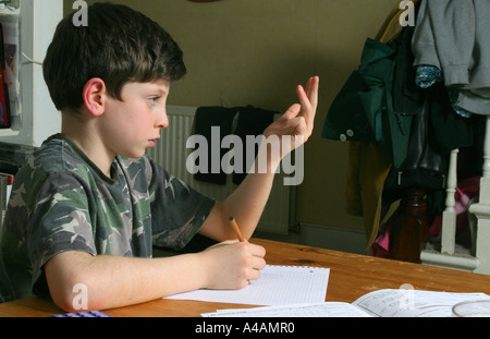 An eight year old boy doing his maths homework at home, February 2006. - Stock Photo