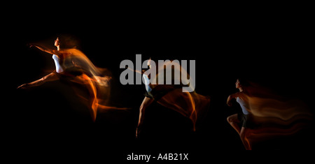 dancer jumping through the air showing motion as trails of light impact - Stock Photo