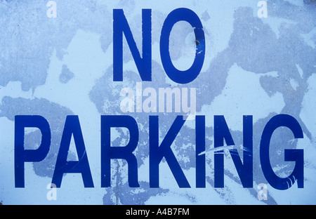 Close up of white blue and grey weathered metal sign stating No parking - Stock Photo
