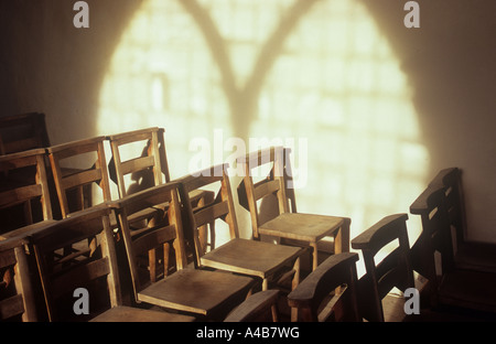 Projection in warm light onto wall of Gothic Decorated style window with plain glass and light streaming onto rows - Stock Photo
