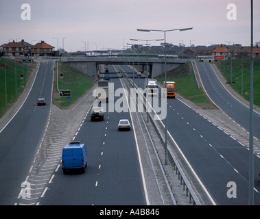 Trunk road intersection showing inclined slip roads, concrete retaining walls, road markings, crash barriers, bridges, - Stock Photo