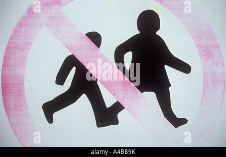 Weathered and faded sign showing two children running hand-in-hand and with red diagonal bar indicating No children - Stock Photo
