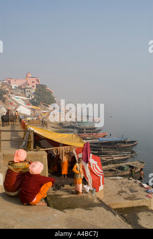 Stock image of two holy men sadhus sadhu sitting down looking over the Mother Ganges - Stock Photo