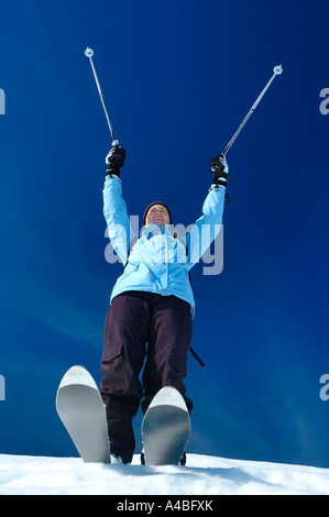 A young woman skier raises her poles in the air in joy - Stock Photo