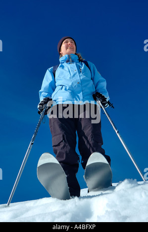 A young woman skier from a low viewpoint - Stock Photo