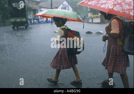 MONSOON STORY, INDIA', GOA. SCHOOL CHILDREN GOING HOME IN HEAVY RAIN IN THE MARKET TOWN OF MAPUSA, 1999 - Stock Photo