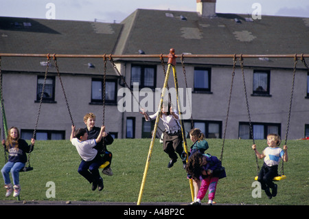 Motherwell, Scotland March 1992. Children  play on swings. Ravenscraig steel works closed in 1992 causing mass unemployment - Stock Photo