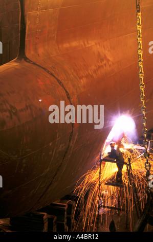 falmouth docks welders work on ship in dry dock - Stock Photo