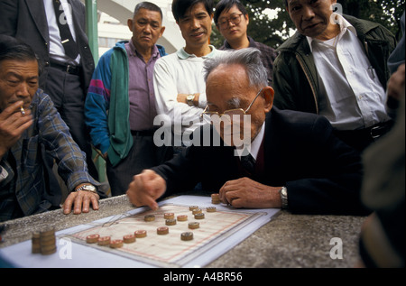 HONG KONG PEOPLE GATHERED AROUND WATCHING OLD MAN PLAYING DRAUGHTS WITH OPPONENT ON THE STREET - Stock Photo