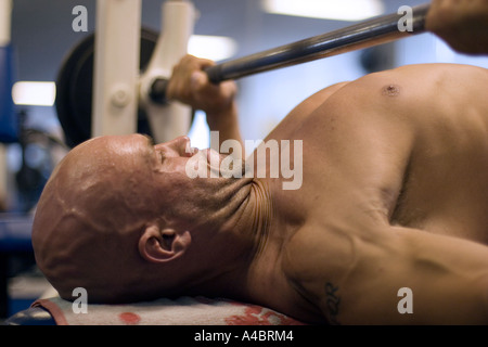 Man exercises on bench press in gym - Stock Photo
