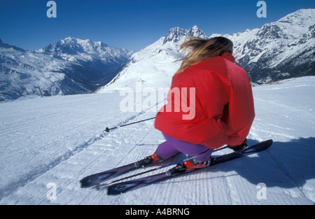 Female skier going down a freshly compacted ski run with the wind blowing through her long blonde hair Near Chamonix - Stock Photo